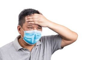 Concerned matured Asian Chinese man with face mask with hand on