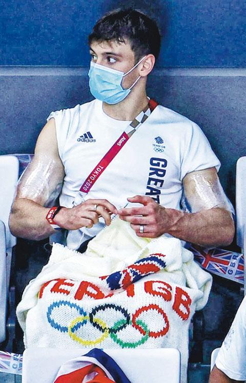 熱愛編織的英國跳水選手戴利,坐在觀眾席上「密密織」。運動心理學家指,運動員在練習以外尋找興趣可減壓,配合靜觀更能訓練專注力。(東京奧運IG圖片)