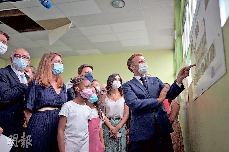 法國的學童周四在新冠疫情持續的情况下,於新學年回校上課,總統馬克龍(右)當日到訪馬賽一間小學,他與在場的學生都有戴上口罩防疫。(路透社)